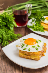 Croque-Madame, a French sandwich with greens and berry juice for breakfast. Wooden table. Top view. Close-up