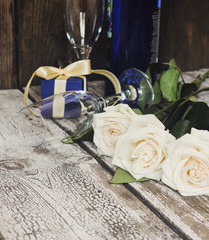 White roses, sparkling wine bottle, champagne glasses on a woode