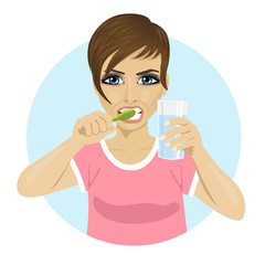 young woman brushing teeth and holding glass of water