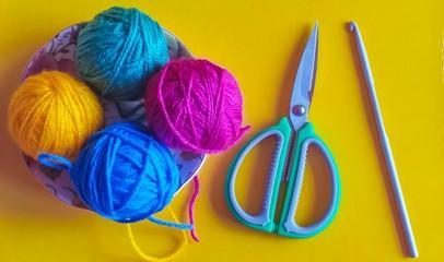 Multicolored knitting yarn balls, crochet hook and scissors on yellow background