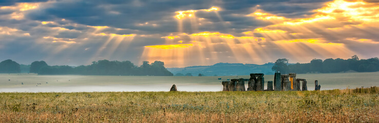 Amesbury, Wiltshire, United Kingdom - August 14, 2016: Cloudy sunrise over Stonehenge - prehistoric megalith monument arranged in circle.