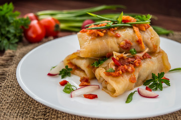 Cabbage rolls in tomato sauce. Wooden background. Close-up