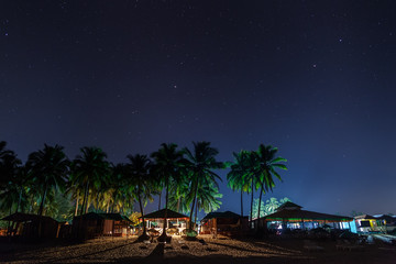 Coastal cafes, restaurants and beach lodges, in night illumination under the star sky, between the palms.