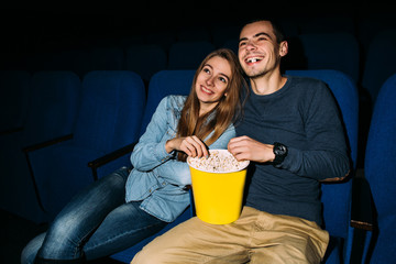 Cinema day. Young happy couple watching funny movie in cinema at their romantic date. World cinema day