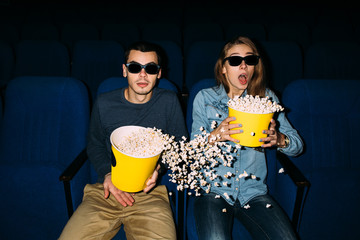 Cinema day. Young couple with popcorn watching interesting movie on their date in cinema. World cinema day concept.