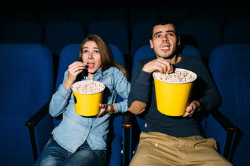 Cinema. Couple watching horror movie and eats popcorn in cinema.  World cinema day concept.
