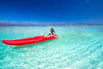 Young caucasian attractive woman with her little son kayaking on tropical island