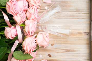 Pink fresh valentines day roses on wood with two champagne glasses
