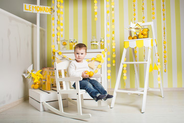 a boy inside a bright decorated white wooden room