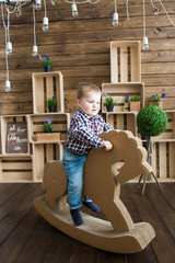 a boy swaying on a wooden horse inside a decorated wooden house