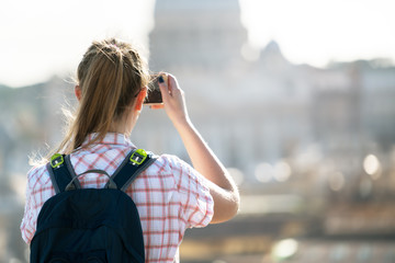 Young woman takes a picture of Saint Peter  Cathedral , Rome, It