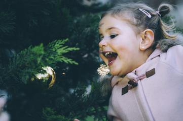Baby decorating pine at christmas