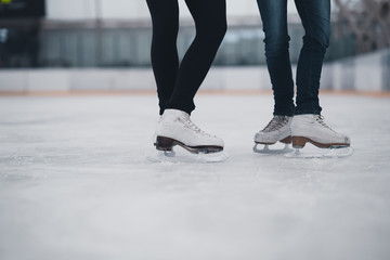 Friends on skates at ice-skating rink.