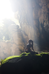 Wall Mural - Silhouette of a young woman practicing yoga in the cave
