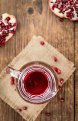 Fresh made Pomegranate juice on rustic background