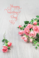 Small pink roses on wood, st. Valentine greeting card, text