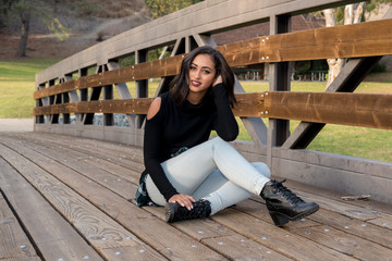 Beautiful female model sitting on a bridge in the park