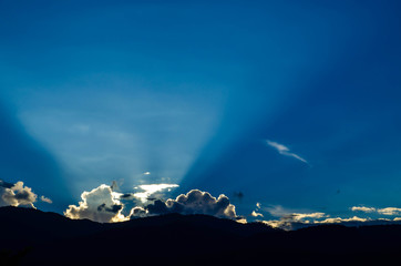 dramatic Sunset with sun rays through clouds and mountain
