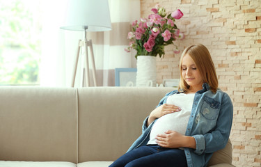 Pregnant woman sitting on couch