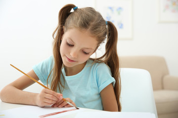 Cute girl painting picture at home