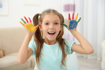 Cute girl with palms in paint at home