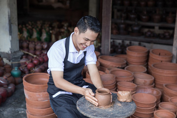 male potter making pot