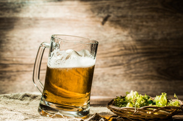 Big mug of beer standing on empty wooden background