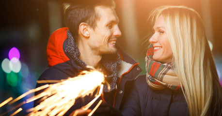 Couple with sparklers on street