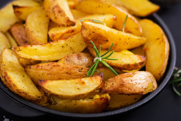 Ruddy Baked potato wedges with rosemary and garlic on a dark background.