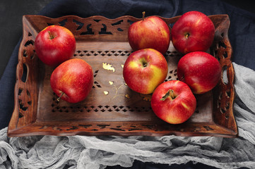 Fresh red apples in wooden tray over blue table runner