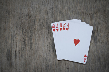 royal flush playing cards isolated on wooden table background