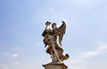 View of winged man statue with clear blue sky background at St. Angelo bridge in Rome. It was built in 134 A.D., with travertine marble fascias & spanning the River Tiber.