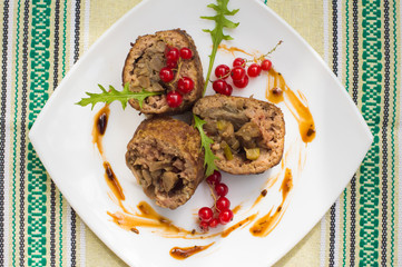 Meatloaf stuffed with mushrooms  sauce and berries. Rustic background. Top view. Close-up
