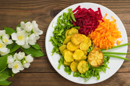 Dish with fried potatoes, beets, carrots and lettuce on a background of flowers. Wooden table. Close-up