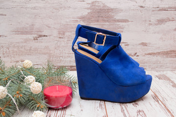 Blue suede shoes on a wooden background, fir branch, garland and candle. fashion concept