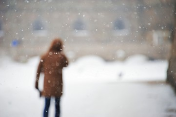 Blurred image of man standing on the street in the yard, during snowfall on a cold winter day.