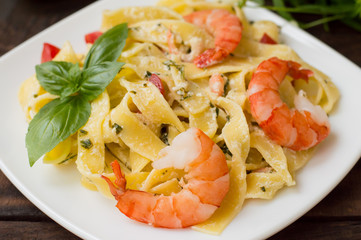 Fettuccine pasta in cream sauce with king prawns on a plate  the wooden table. Horizontal view from above. Top . Close-up
