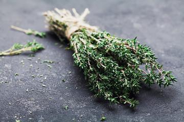 Herb thyme on black kitchen table closeup.