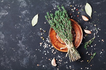 Food background of herb thyme and spices on black kitchen table top view.