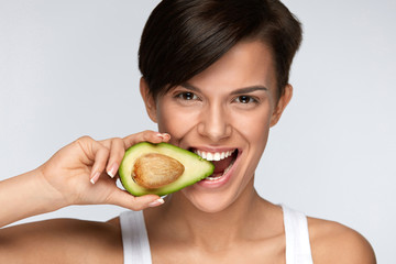 Nutrition. Beautiful Smiling Woman Biting Organic Green Avocado