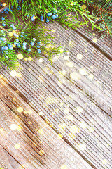 Christmas background. Green Fir with gold bokeh on old wooden .