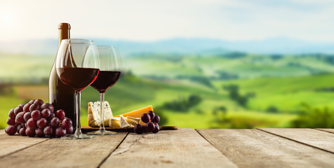 Fotobehang Wijngaard Red wine served on wooden planks, vineyard on background