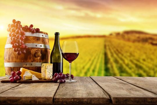 Red wine served on wooden planks, vineyard on background