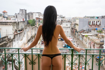 Young naked slender tall woman with long black hair stands alone