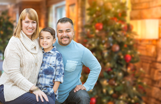 Happy Young Mixed Race Family Portrait In Front of Christmas Tree Indoors.