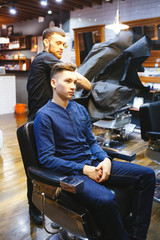 hairdresser makes hairstyle for a young man