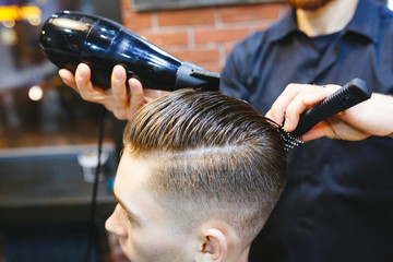 man getting groomed by hairdresser with hair dryer at barbershop