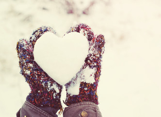Girl with heart from snow in knitted mittens in the winter. Love concept. Valentine background.