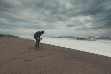 Giovane ragazzo che fotografa vicino l'oceano tempestoso.