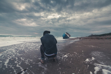 Uomo fotografo di fronte a una barca di immigrati clandestini arenata sulla spiaggia. Fotografie estreme concetto.